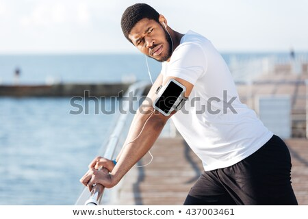 Sportsman listening to music from cell phone on the beach Stock photo © deandrobot