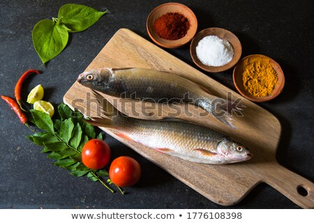 Raw whole fish with vegetables and spices on natural slate stone Stock photo © tab62
