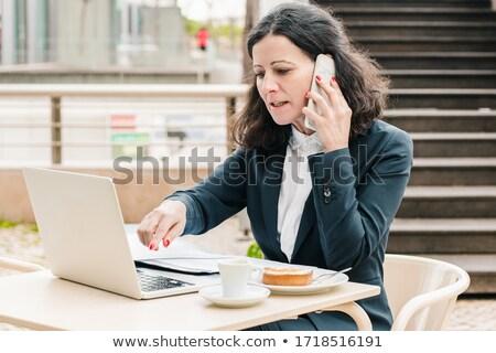 serious woman talking on mobile phone on the street stock photo © stevanovicigor
