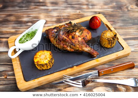 Tasty Grilled chicken lag and rosemary on wooden background. Stock photo © Yatsenko