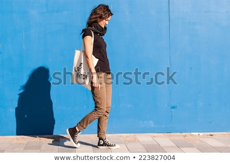 Jeune fille marche trottoir mur porte shirt Photo stock © IS2
