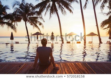 Férfi utazó tenger kövek fa néz Stock fotó © artfotodima