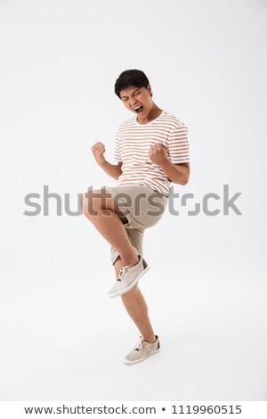 Tam uzunlukta fotoğraf yakışıklı adam çizgili tshirt atlama Stok fotoğraf © deandrobot