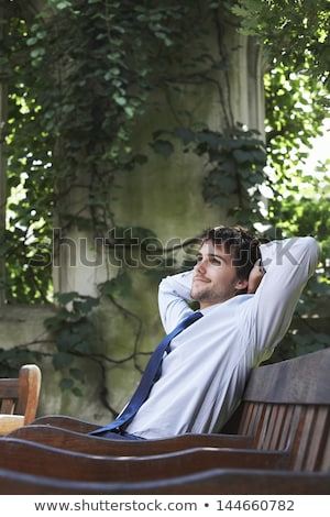 happy young businessman sitting on a bench outdoors stock photo © deandrobot