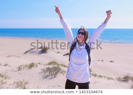 Happy young brunette woman open her arms to the sky and sea  Stock photo © dashapetrenko