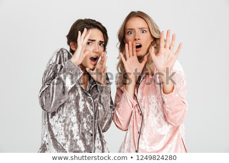 Two scared girls wearing pajamas isolated Stock photo © deandrobot