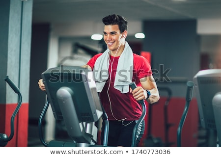 Man doing exercise on elliptical cross trainer in sport fitness  Stock photo © boggy