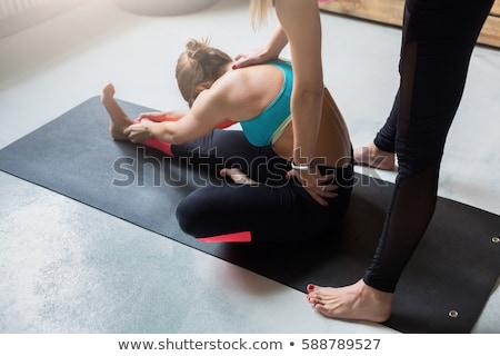 Instructor assisting woman to make yoga pose Stockfoto © Kzenon