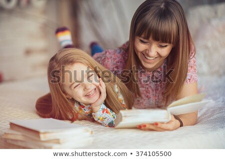 Portrait of a mother and daughter reading a book lying and relax in the bed Stok fotoğraf © Lopolo