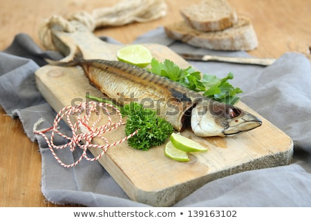 Smoked mackerel with lime and parsley on wooden board Stock photo © Melnyk