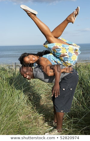 Energetic Young Couple Having Fun In Dunes By Beach Stock photo © monkey_business