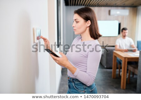 young woman with smartphone loading smart remote control application in touchpad stock photo © pressmaster