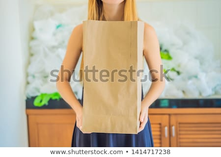 Paper bag amid a pile of plastic bags. Zero waste concept. The concept of World Environment Day Stock photo © galitskaya