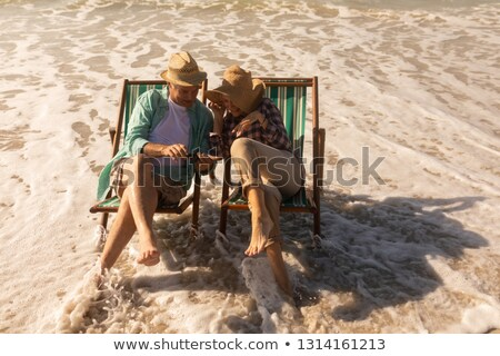High angle view of active senior couple relaxing in a sun lounger on the beach  Stock photo © wavebreak_media