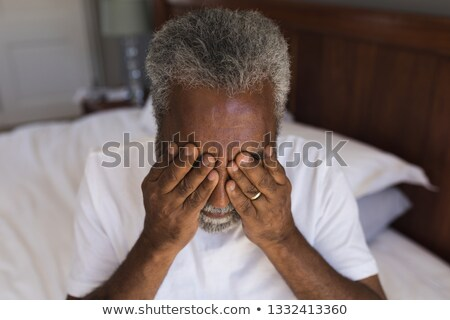 Portrait of a worried senior African American man covering his eyes in bedroom at home Stock photo © wavebreak_media