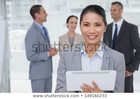 Portrait of attractive Caucasian female executive smiling while using digital tablet in office with  Stock photo © wavebreak_media