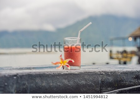 A glass of guava juice on the background of a lake and mountains. Healthy eating concept Stock photo © galitskaya