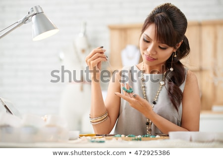 Woman making a necklace from gemstones Stock photo © Kzenon