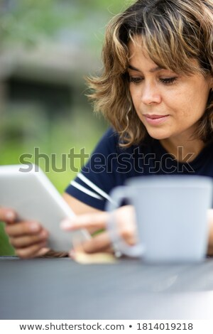 smiling woman with ebook reader, coffee at a table with books Stock photo © Rob_Stark