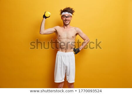 Male instructor posing with raised dumbbell stock photo © stockyimages