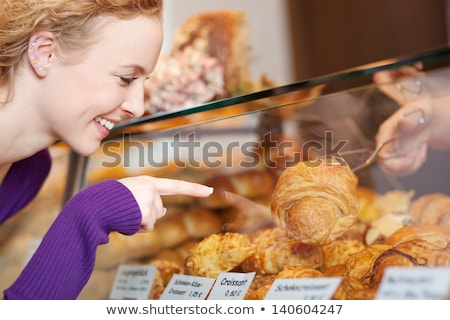 happy young woman selecting bread from display cabinet of bakery stock photo © hasloo