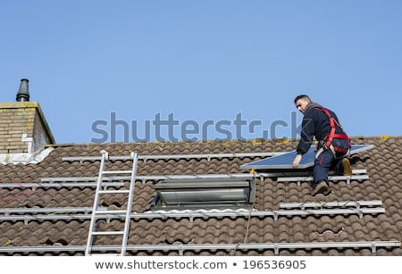 Stock photo: man putting the solar panel on the roof