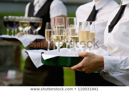 waitress filling glasses with champagne stock photo © kzenon