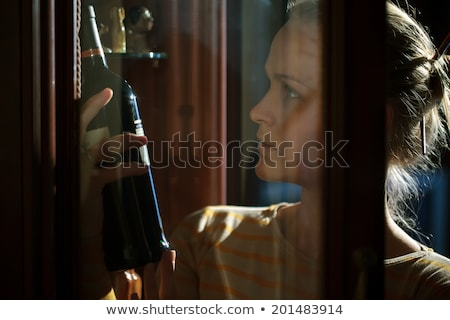 Woman taking a bottle of wine from liquor cabinet Stock photo © d13