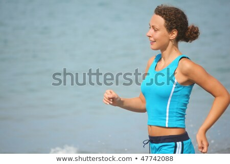 Smiling woman wearing sporty clothers is running near water. sea in out of focus. Stock photo © Paha_L