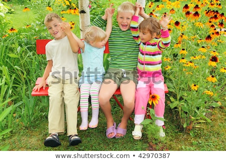 Children sitting on bench in garden, having joined hands Stock photo © Paha_L