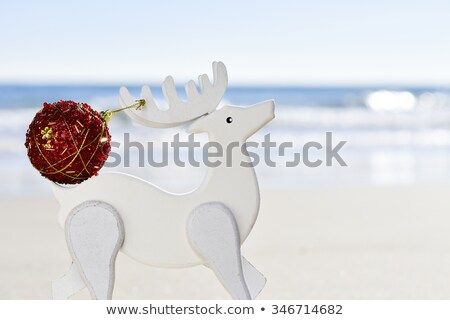 christmas ball in the antler of a wooden reindeer on the beach Stock photo © nito