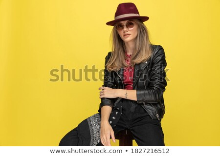 blonde in leather jacket posing seated on stool in studio Stock photo © feedough
