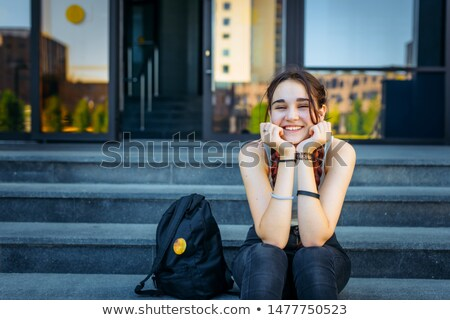 Smiling pretty young woman with two long braids in glasses  Stock photo © deandrobot