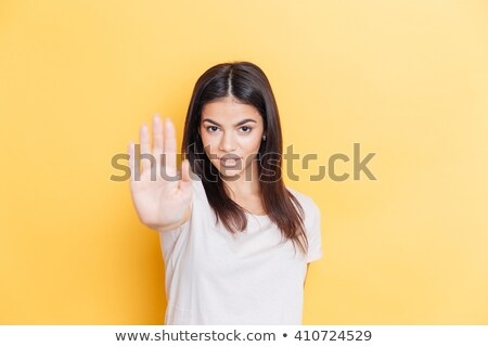 Cute woman showing stop gesutre with palm Stock photo © deandrobot