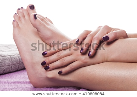manicured hands stroke bare feet with nail polish stock photo © juniart