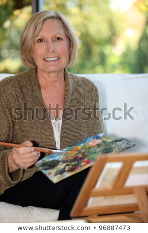 Happy woman painter with red hair outdoors. Stock photo © deandrobot