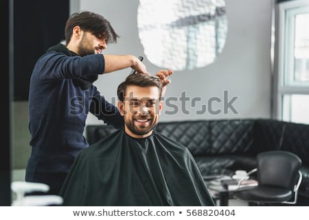 Happy man getting haircut by hairdresser with scissors Stock photo © deandrobot