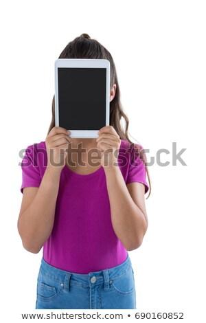 Teenage girl hiding her face behind digital tablet Stock photo © wavebreak_media