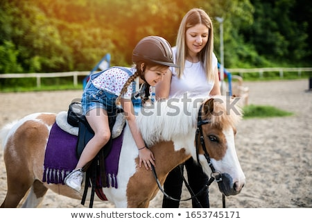 Happy female jockey with sister standing by horse Stock photo © wavebreak_media