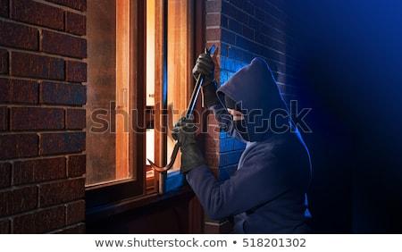 Burglar using a crowbar to break into a house Stock photo © stokkete