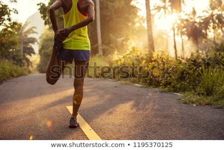Stock photo: Jogger stretching in forest