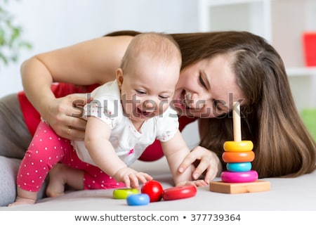 mother and baby daughter playing with pyramid toy stock photo © dolgachov