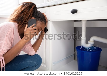 woman calling plumber in front of leaking from sink pipe stock photo © andreypopov