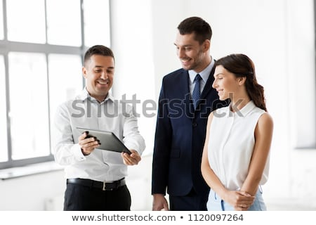 realtor showing tablet pc to customers at office stock photo © dolgachov