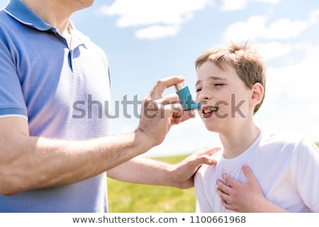 child using inhaler for asthma outside in a park with his father Stock photo © Lopolo