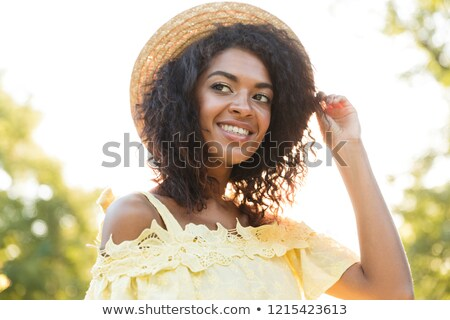 smiling american woman 20s wearing straw hat and dress sitting stock photo © deandrobot