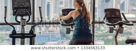Stockfoto: Young Woman On A Stationary Bike In A Gym On A Big City Background Banner Long Format