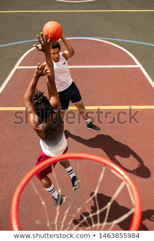 One of young intercultural basketball players attacking the ball of rival Stock photo © pressmaster