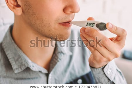 man measuring oral temperature by thermometer Stock photo © dolgachov