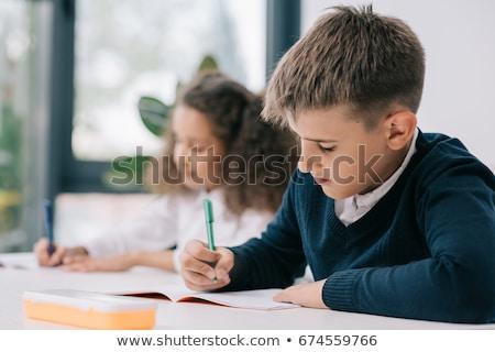 Sorridente aluna sessão secretária olhando Foto stock © wavebreak_media